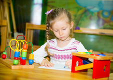 Förtjusande barnflickateckning med färgrika blyertspennor i barnkammarerum Unge i dagis i Montessori förskole- grupp Arkivbild