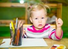 Förtjusande barnflickateckning med färgrika blyertspennor i barnkammarerum Unge i dagis i Montessori förskole- grupp Arkivfoto