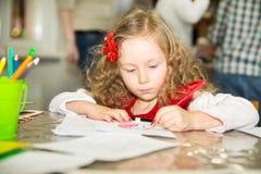Förtjusande barnflickateckning med färgrika blyertspennor i barnkammarerum Unge i dagis i Montessori förskole- grupp Arkivfoton
