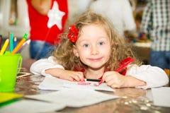 Förtjusande barnflickateckning med färgrika blyertspennor i barnkammarerum Unge i dagis i Montessori förskole- grupp Royaltyfri Foto