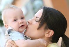 förtjusande behandla som ett barn den lyckliga modern för pojkefamiljen Arkivfoton