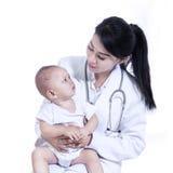 Förtjusande doktor med en behandla som ett barn i henne isolerade armar - Royaltyfria Foton