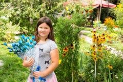 Förtjusande flicka för litet barn med buketten av blommor på lycklig födelsedag Grön naturbakgrund för sommar Royaltyfri Fotografi