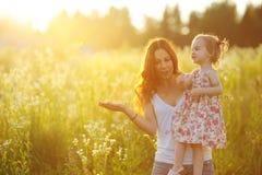 förtjusande flicka henne holdingmoderbarn Royaltyfria Bilder