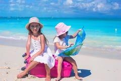 Förtjusande flickor med den stora resväskan och översikten på Arkivfoto