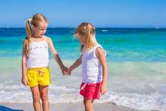 Förtjusande gulliga flickor har gyckel på den vita stranden under Arkivbild