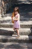Förtjusande liten flicka som går och rymmer en släntra av bröd Arkivfoton