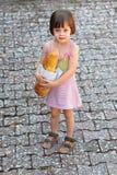 Förtjusande liten flicka som rymmer en släntra av bröd Arkivfoton
