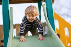 Förtjusande litet barnpojke som har roligt och glider på utomhus- playgroun Fotografering för Bildbyråer