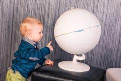 Förtjusande nyfiket behandla som ett barn pojken med ett jordklot Royaltyfri Foto