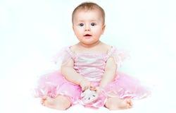 Förtjusande små behandla som ett barn flickan i rosa färgklänningen som spelar med hennes rosa sko Arkivbild