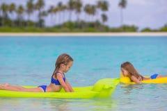 Förtjusande små flickor på luftuppblåsbarmadrassen Arkivfoto