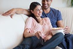 Förtjust koppla ihop hållande ögonen på TVstunder som äter popcorn Royaltyfri Bild