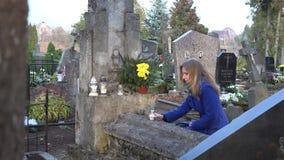 Fru för ung kvinna som sörjer nära grav i stadskyrkogård 4K arkivfilmer