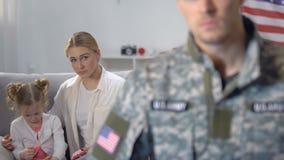Fru och dotter som ser maken i den militära likformign som lämnar för att arbeta, arbetsuppgift lager videofilmer