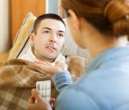 Fru som ger preventivpillerar till den sjuka mannen royaltyfri foto