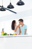 Fru som matar hennes make i deras kök Royaltyfri Fotografi