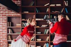 Fru som poserar till hennes make som över tar foto av hennes bokhyllor royaltyfria bilder