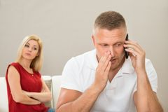 Fru som ser maken som talar på mobiltelefonen royaltyfria foton