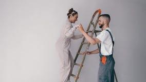 Fruanseende på en stege, medan hennes make målar väggen lager videofilmer