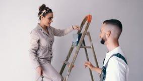 Fruanseende på en stege, medan hennes make målar väggen arkivfilmer