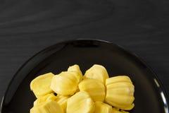 Frucht der gelben Steckfassung auf hölzernem Schwarzweiss-Hintergrund, Beschneidungspfad Lizenzfreies Stockbild
