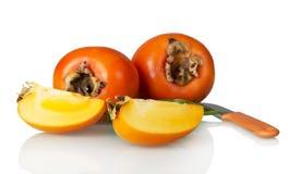 Frucht der Persimone, der geschnittenen Stücke und des Messers lokalisiert auf Weiß Lizenzfreie Stockbilder