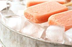 Frucht-Eis am Stiel auf Eis mit Erdbeere, Orange, Ananas, Mango lizenzfreie stockfotos