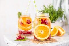 Frucht goss Detox-Wasser mit orange roten Johannisbeeren und Rosmarin hinein Stockfotografie