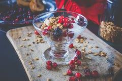 Frucht-, Hafer-und Nuss-Granola mit Jogurt und Himbeeren Stockfotos