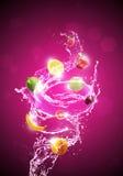 Frucht im Wasser-Spritzen-Rot-Hintergrund Lizenzfreie Stockfotos