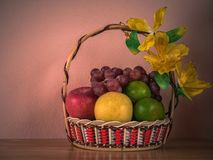 Frucht-Korb auf Holztisch mit konkretem Hintergrund der Wand, WTI lizenzfreies stockbild