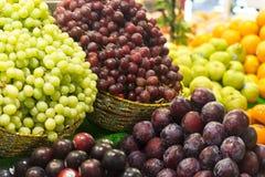 Frucht-Stall mit Trauben und Pflaumen Stockfoto
