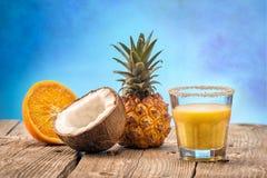 Fruchtananas smooties mit Kokosnuss und Orange auf dem Holztisch lokalisiert auf blauem Hintergrund Stockbilder