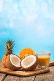 Fruchtananas smooties mit Kokosnuss und Orange auf dem Holztisch lokalisiert auf blauem Hintergrund Stockbild