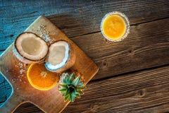 Fruchtananas smooties mit Kokosnuss und Orange auf Holztisch mit Blaulicht Stockfoto