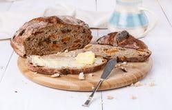 Fruchtbrot mit Butter auf weißem hölzernem Hintergrund Stockfoto