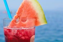 Fruchtcocktail mit Wassermelonenscheibe auf einem Strand Stockbild