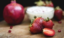 Fruchtcreme auf hölzernem Brett mit Granatapfel und anderen Erdbeeren in einem dunklen Hintergrund lizenzfreie stockfotografie