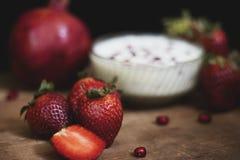 Fruchtcreme auf hölzernem Brett mit Granatapfel und anderen Erdbeeren in einem dunklen Hintergrund lizenzfreies stockfoto