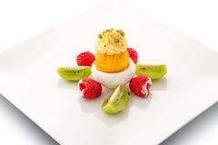 FruchtEiscreme mit Pistazien, Kiwi und frischen Himbeeren auf weißer Platte, exklusiver Sommernachtisch, Konditorei Lizenzfreies Stockfoto