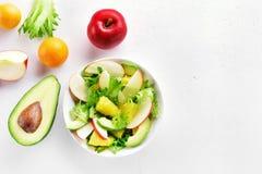 Fruchtgemüsesalat mit roten Äpfeln, Avocado, orange Scheiben Stockbilder