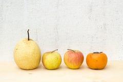 Fruchtgruppenstillleben auf Sperrholz und Betonmauer Lizenzfreie Stockfotos
