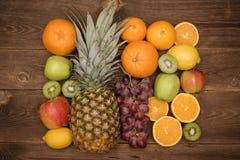 Fruchthintergrund mit Orange, Kiwi, Traube, Äpfeln und Zitrone auf dem Holztisch Stockbild
