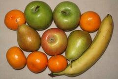 Fruchthintergrund von den Äpfeln, von den Bananen und von den Tangerinen auf entworfen Lizenzfreie Stockfotos