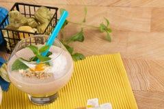Fruchtiger Smoothie im Nachtischglas mit blauem Stroh auf einem gelben Hintergrund Cocktails mit getrockneten Aprikosen, Eiscreme Stockfotografie