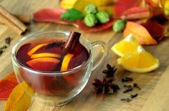 Fruchtiger Tee mit Zimt, Nelken und Sternanis Heißes würziges Getränk Rot und Orange färbt Efeublattnahaufnahme Stockbild