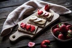 Fruchtiger Toast auf hölzernem Hintergrund Erdbeeren, Brot, Butter und Käse Abbildung der roten Lilie Lizenzfreie Stockfotos
