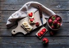 Fruchtiger Toast auf hölzernem Hintergrund Erdbeeren, Brot, Butter und Käse Abbildung der roten Lilie Lizenzfreie Stockfotografie