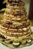 Fruchtkeks-Mehrfarbenhochzeitstorte auf einem großen Stand gemacht vom Holz abgestufte Hochzeitstorte auf einem hölzernen Hinterg lizenzfreie stockfotos